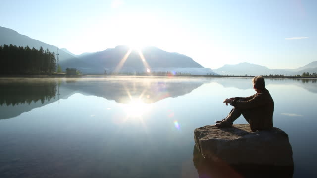 Man relaxes on island rock in mountain lake, looks off