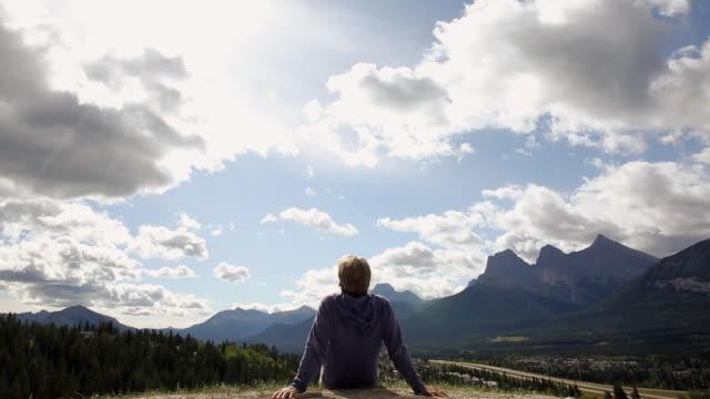 man relaxes on mountain ridge, looks off - endast en medelålders man bildbanksvideor och videomaterial från bakom kulisserna