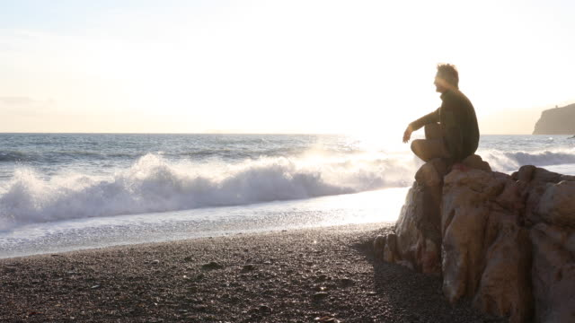 Man relaxes on rock above beach, surf