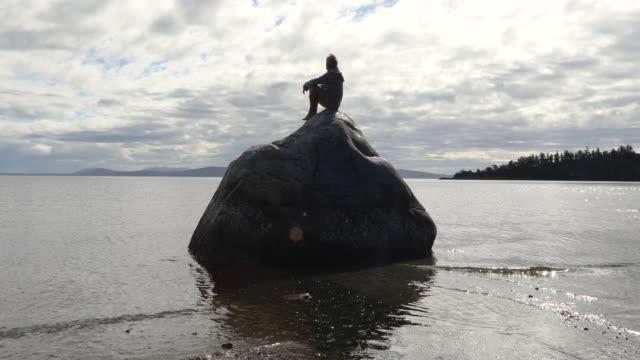Man slappnar av på klippa ovanför grunt hav, vid soluppgången