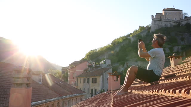 Man relaxes on roof in medieval village, takes pic with phone