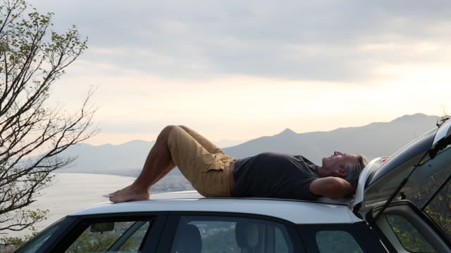 vidéos et rushes de man relaxes on roof of car, hills and sea distant - être étendu