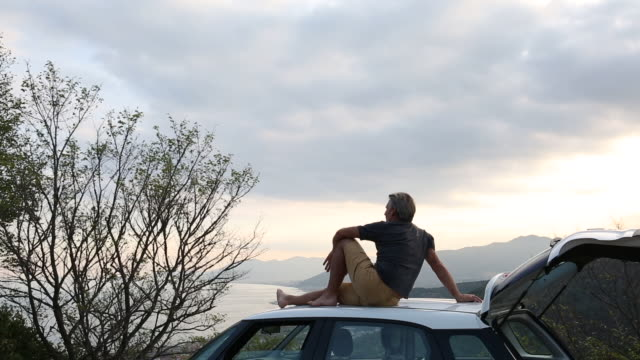 Man relaxes on roof of car, hills and sea distant