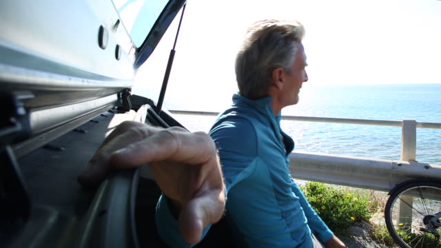 Man relaxes on tailgate of car, looks out over sea
