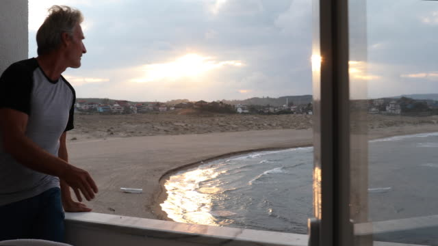 man relaxes on veranda edge above beach and surf - porch stock videos & royalty-free footage