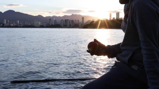 man slappnar med apple för att se över stadssilhuetten - äpple bildbanksvideor och videomaterial från bakom kulisserna