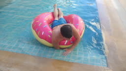 Man relaxes with inflatable tube, in tropics