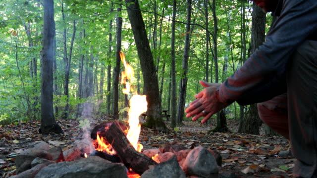 man slappnar av och håller värmen vid brasan på camping hösten - utomhusaktivitet bildbanksvideor och videomaterial från bakom kulisserna