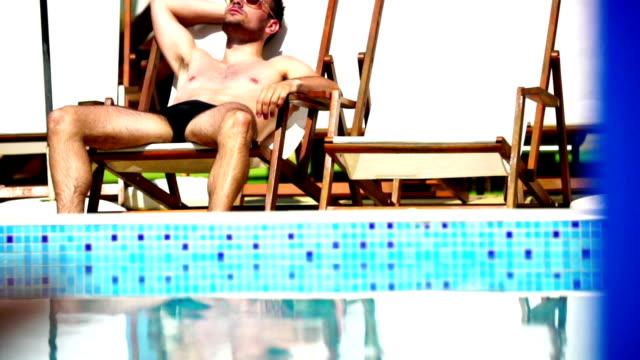 vídeos de stock, filmes e b-roll de homem relaxante à beira da piscina. - calções de corrida