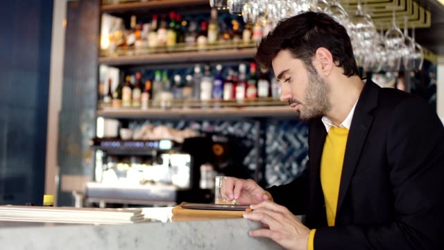 man relaxing at the bar after work - 30 34 years video stock e b–roll
