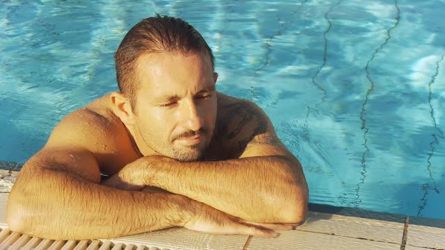 hd: uomo rilassante sul bordo piscina - bordo piscina video stock e b–roll