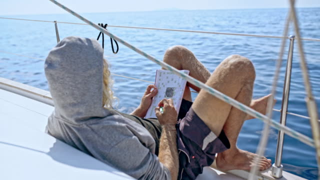 4k man relaxing, doing crossword puzzle on sunny sailboat, real time - hooded top stock videos & royalty-free footage