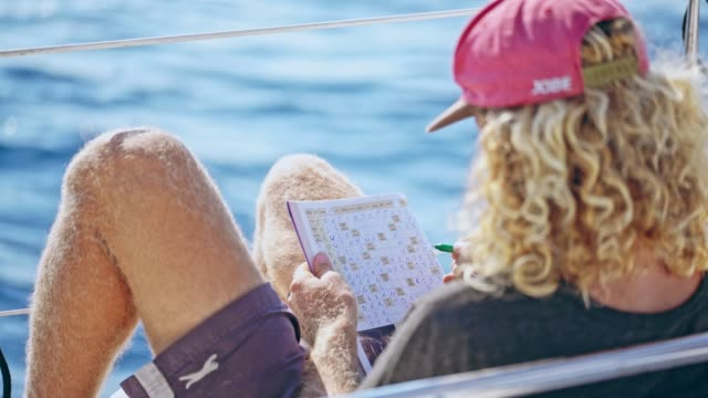 4k man relaxing, doing crossword puzzle on sunny sailboat, real time - crossword stock videos and b-roll footage