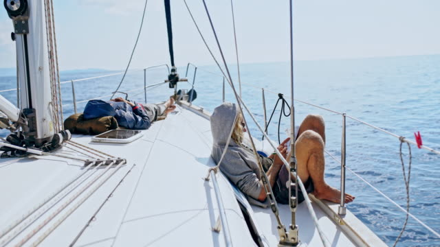 4k man relaxing, doing crossword puzzle on sunny sailboat - crossword stock videos and b-roll footage