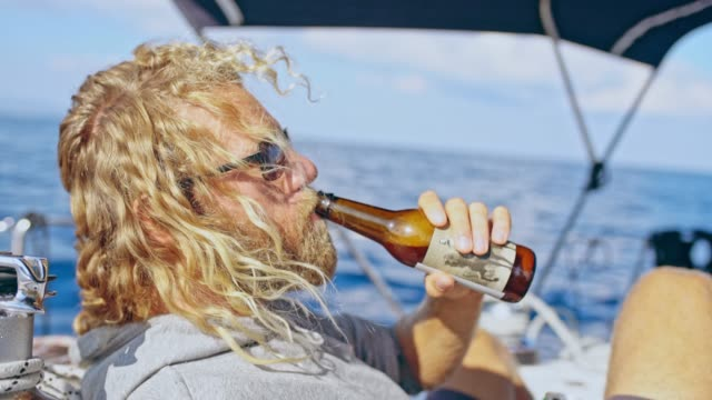 4K Man relaxing, drinking beer on sunny sailboat, real time