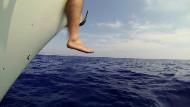 mann entspannend während der kreuzfahrt auf einem segelboot - kiel rumpf stock-videos und b-roll-filmmaterial