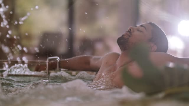 man relaxing in a hot tub at spa - vasca da bagno video stock e b–roll