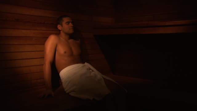 vidéos et rushes de a man relaxing in a sauna - sauna