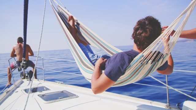 Man relaxing in hammock, drinking beer on sunny sailboat, real time