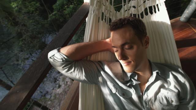 ha, cu, man relaxing in hammock on balcony overlooking forest river, mossman, queensland, australia - einzelner mann über 30 stock-videos und b-roll-filmmaterial