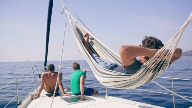 vídeos de stock e filmes b-roll de man relaxing in hammock on sunny sailboat - cama de rede