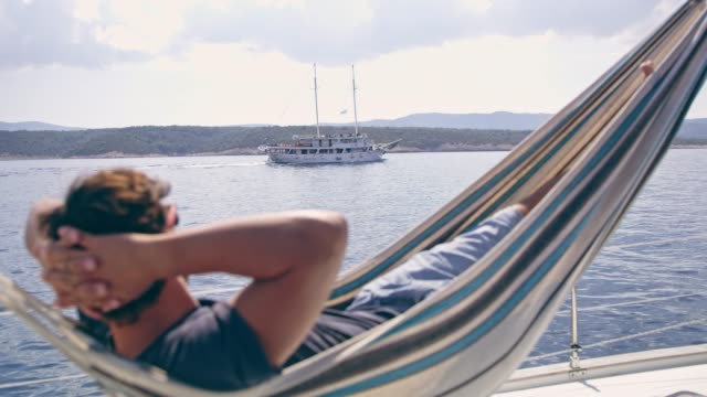 man relaxing in hammock on sunny sailboat - yachting stock videos & royalty-free footage