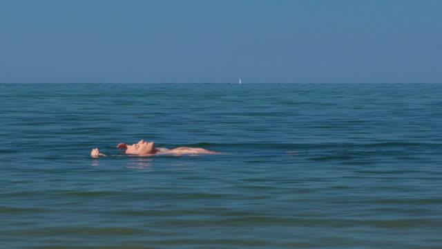 MS, Man relaxing in ocean, North Truro, Massachusetts, USA