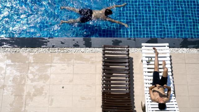 vídeos y material grabado en eventos de stock de hombre relajante en la piscina mientras otro hombre nada - bañador de natación