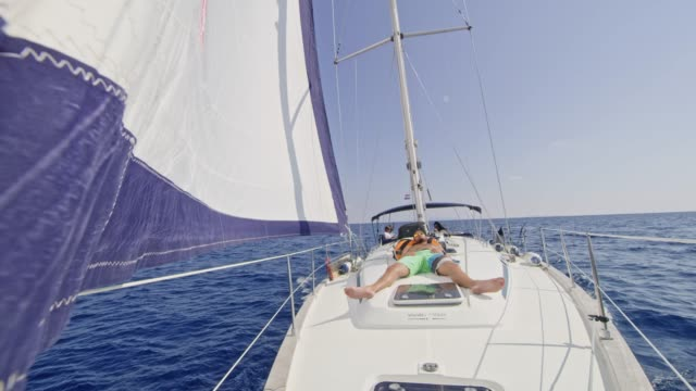 Man relaxing, napping on sunny sailboat, real time
