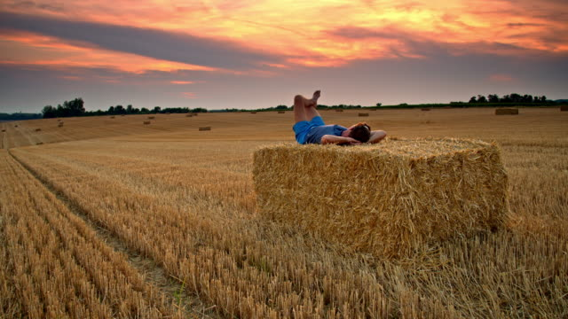 DS Man relaxing on a bale at sunset