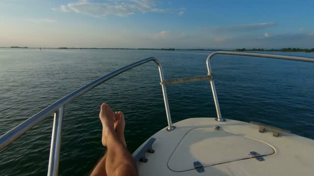man relaxing on a boat in the grado lagoon, italy - kamerafahrt auf schienen stock-videos und b-roll-filmmaterial