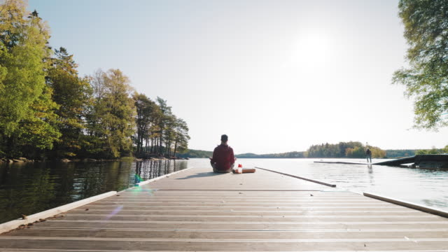man relaxing on a jetty after exercising outdoors - jetty stock videos & royalty-free footage