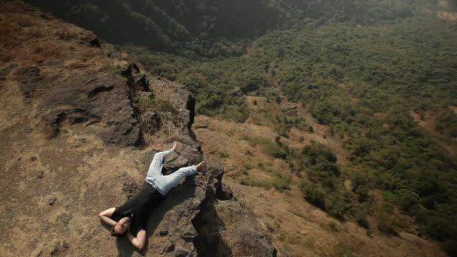 man relaxing on the cliff of mountain  - valley stock videos & royalty-free footage