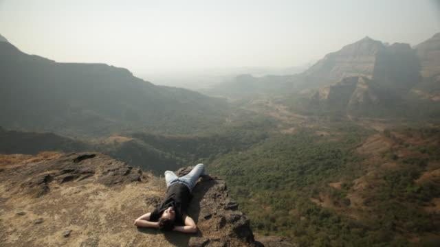 man relaxing on the cliff of mountain  - auf dem rücken liegen stock-videos und b-roll-filmmaterial