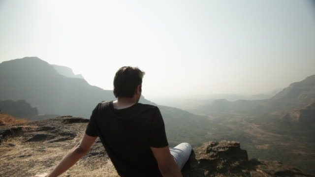 Man relaxing on the cliff of mountain
