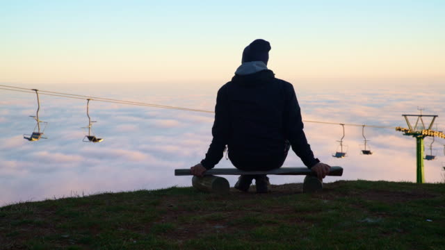 Man relaxing on the top of a hill