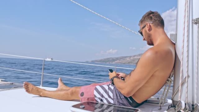 4k man relaxing, using smart phone on sunny sailboat, real time - summer reading stock videos & royalty-free footage