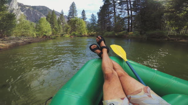 pov man relaxing while rafting in merced river of yosemite - cross legged stock videos & royalty-free footage