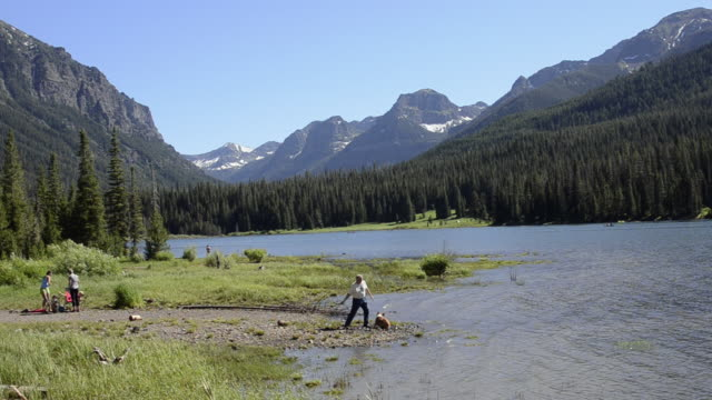 WS Man relaxing with dog and family near lake at gallatin national forest / Boston, Montana, United States