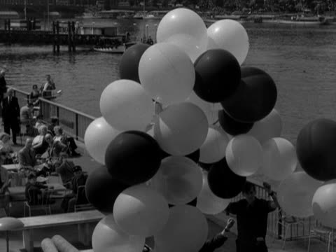 a man releases a bunch of balloons at the festival of britain site on the south bank of the river thames 1951 - festival of britain stock videos & royalty-free footage