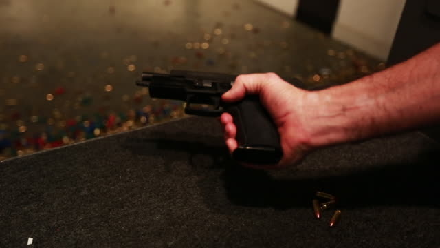 stockvideo's en b-roll-footage met man reloads hand gun, close up shot - pistool handwapen