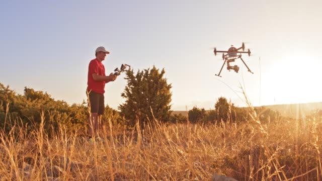 vídeos y material grabado en eventos de stock de hombre ds remoto controlar su drone aterrizando en la cima de una colina al atardecer - operar