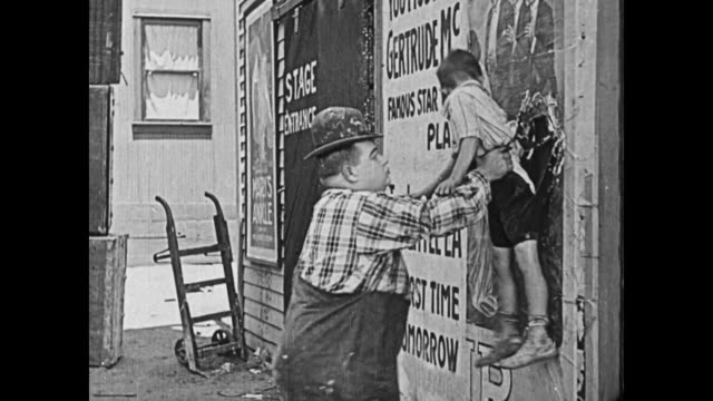 1919 Man (Fatty Arbuckle) removes a boy who is pasted to the wall, and upon noticing that the backside of the boys' pants remain stuck to the wall, he wraps him in a theater poster to cover his exposed underwear