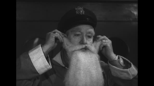 vídeos de stock, filmes e b-roll de man removes a uniform jacket and british army cap and puts on a santa claus costume, beard and a white wig / an audience of large group of children... - british military