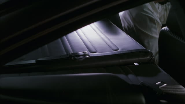 a man removes a weapon from a compartment in the back of a car. - storage compartment stock videos and b-roll footage