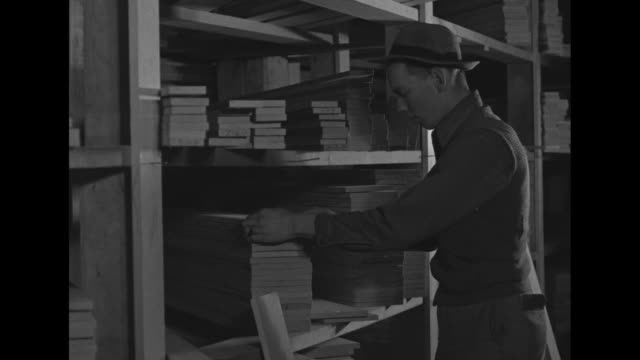 man removes boards from shelves filled with boards and examines them / two men stacking boards / two shots of man examining stacked boards / two... - anacortes stock videos & royalty-free footage