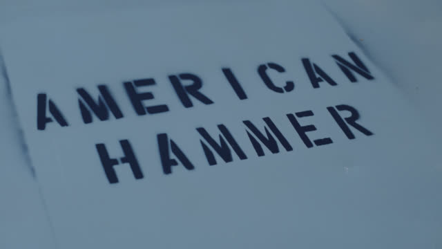cu man removes cardboard stencil to reveal text 'american hammer' spray painted on surface - sign stock videos & royalty-free footage