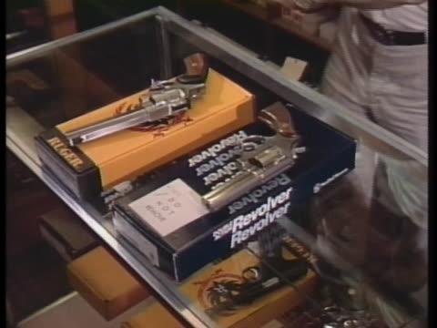 man removes handguns from a display case. - skåp med glasdörrar bildbanksvideor och videomaterial från bakom kulisserna