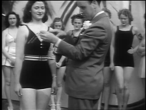 b/w 1941 man removes woman's glasses / pokes fingers through empty frames / swimsuit contest / nj - spielkandidat stock-videos und b-roll-filmmaterial