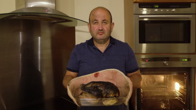 man removing a burnt chicken from oven - burnt stock videos & royalty-free footage